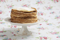 A stack of pancakes on a cake stand