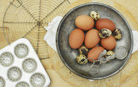qualis and chicken eggs in a metal bowl with vintage baking equipment on a wooden chopping board 22199080421| 写真素材・ストックフォト・画像・イラスト素材|アマナイメージズ