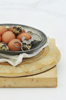 A metal bowl of quail and chicken eggs on a pile of wooden chopping boards
