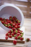 Fresh strawberries falling out of a colander 22199080429  写真素材・ストックフォト・画像・イラスト素材 アマナイメージズ