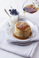 A stack of pancaks being dizzled with maple syrup