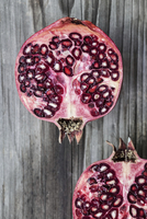 Two pomegranate halves on a wooden surface (view from above) 22199080548| 写真素材・ストックフォト・画像・イラスト素材|アマナイメージズ