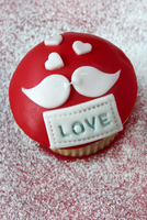 A cupcake iced with the word LOVE and a pair of lovebirds, for Valentine's Day