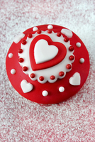 A cupcake with red and white icing and hearts