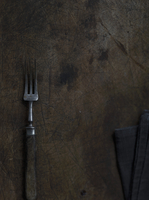 An old fork and a cloth napkin on a wooden surface