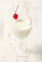 Coconut liqueur with milk and a glace cherry
