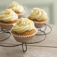 Cupcakes with vanilla cream on a cooling rack
