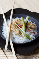Rice noodles with sesame chicken and spring onions (Asia)