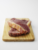 Two beef steaks on chopping board