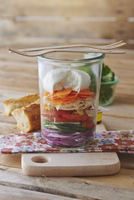 A layered salad with vegetables and mozzarella in a glass