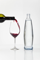 Red wine being poured into a glass, next to a bottle of water