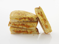Toasted sandwiches, stacked, against a white background