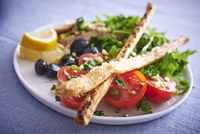 Tomato salad with olives and breadsticks
