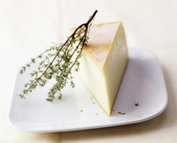 A wedge of Raclette cheese with a sprig of fresh thyme on a plate