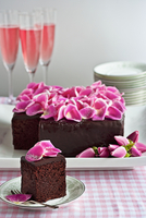 Chocolate cake decorated with pink rose petals and served with champagne cocktails