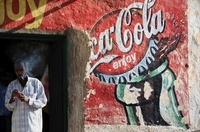 Man smoking in doorway of shop with painted Coca Cola sign,