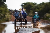 Crossing a flooded road by motorbike and donkey cart on the