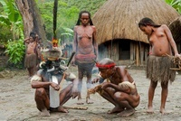 Dani tribespeople making fire in their traditional village,