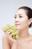 Close-up Of Young Woman Holding A Bunch Of Grapes