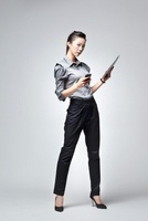 A young woman in a business suit posing with an iPad and an
