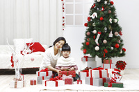 Mom and daughter surrounded by gift boxes sitting in front o