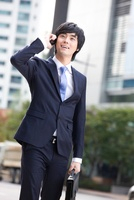 A young man in a business suit talking on the phone,Korean