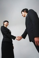 A young couple in business suits shaking hands,Korean