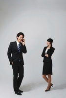 A young couple in business suits talking on their cellphones