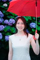 あじさいの花と雨傘をさす笑顔の女性
