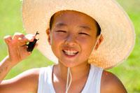 麦わら帽子をかぶりカブトムシを持つ少年