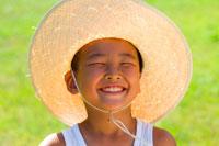 麦わら帽子をかぶり笑顔の男の子
