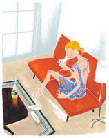 ソファでマニキュアを塗る女性