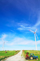 風力発電の風車と牧草ロールとトラクター