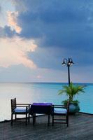 テーブルセットと明かりと夕日と海