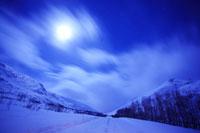 月夜の流雲と道路と雪山の山並み