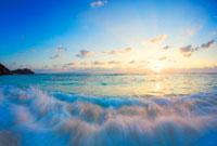 渚に打ち寄せる波と夕日