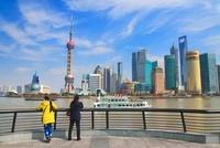 東方明珠塔と浦東新区のビル群と黄浦江と中国人女性と遊覧船