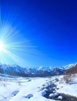 松川と白馬連峰など北アルプスの冬の山並みと太陽の光芒