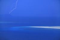 嘉比島の砂州と阿波連岬灯台に落ちる雷