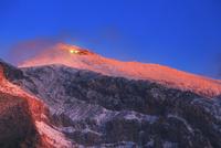 三笠山から望む御嶽山のモルゲンロートと朝日に輝く山荘