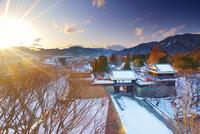 大河ドラマ館から望む雪景色の上田城と夕日の光芒