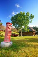 タプコプ創遊村の郵便ポストと古民家 22320041301| 写真素材・ストックフォト・画像・イラスト素材|アマナイメージズ