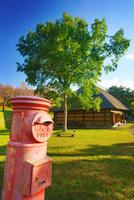 タプコプ創遊村の郵便ポストと古民家 22320041304| 写真素材・ストックフォト・画像・イラスト素材|アマナイメージズ