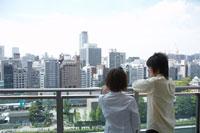 ベランダから市内を眺めるカップル