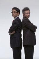 背中合わせで立っている二人のビジネスマン
