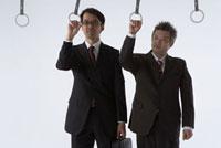 吊革につかまっている二人のビジネスマン