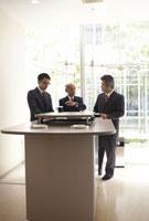 喫煙ルームで話をしている3人のビジネスマン