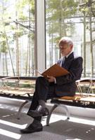 窓ぎわの椅子に座って書類を見るビジネスマン 22321024705| 写真素材・ストックフォト・画像・イラスト素材|アマナイメージズ