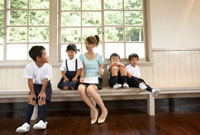 ベンチで話する小学生と女性教師