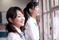 窓から外を眺める2人の女子学生